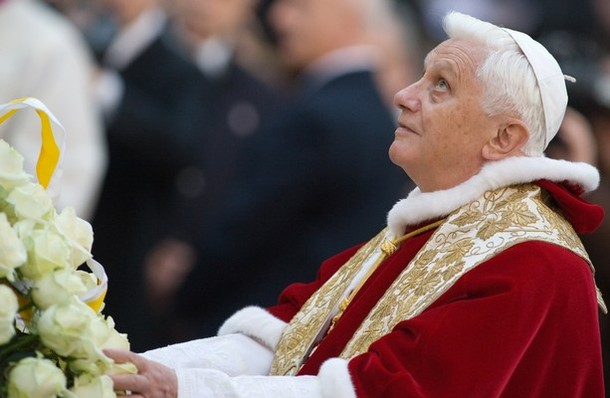 The Holy Father laying a bouquet of white roses at the feet of the Virgin